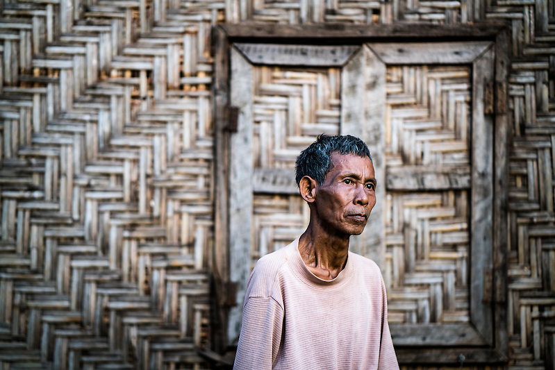 MYITKYINA, MYANMAR - MARCH 12th, 2016: Sin Hwa, 60, at his new home in Aungmyinthar Village. He was forced to move here in 2011 when the Myitsone Dam project was supposed to flood the land he lived and farmed on. In this village, there is no land for cultivation, and he's only able to do day labor jobs for income, which are inconsistent. The dam project was stalled not long after they moved, and still remains on hold. It still remains unclear whether Myanmar's newly elected government will resume or cancel the project, which is largely unpopular in Kachin State, as it would flood large swaths of land, and the majority of electricity it would produce would be delivered to China. (Quinn Ryan Mattingly/For The Washington Post)