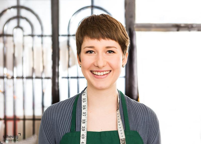 Junge Frau in ihrem Geschäft/Workshop, Wien, Österreich, Jungunternehmerin im Kreativbereich, Portrait, Maßband, Schürze (Dieter Schewig)