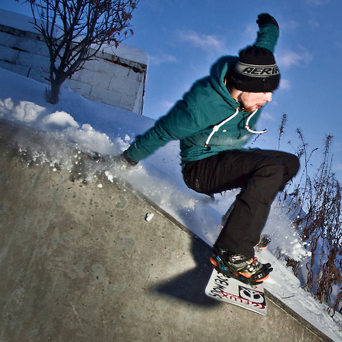 Urban snowboarder, Chris Brewster, performs a Wallie Fronline 270 on the 5th Avenue Hill across from Elderberry Park, downtown Anchorage (Clark James Mishler)