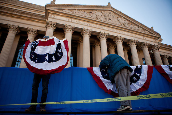 Travon Bristol, left, and Ken Hines hang bunting in front of the National Archives for the presidential inaugural parade, January 20, 2013 in Washington, D.C. (Max Whittaker)
