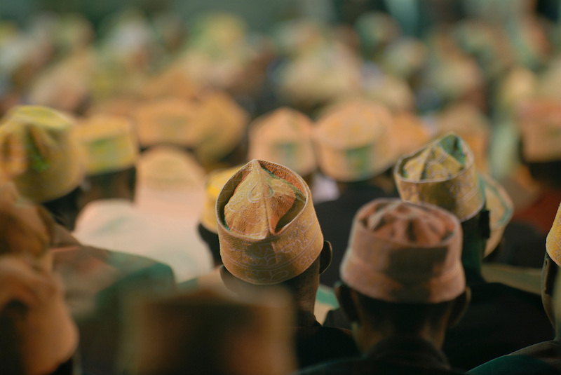 The heads and caps of many men in a mosque at a wedding. Comores. Grand Comore. (Michael Runkel)