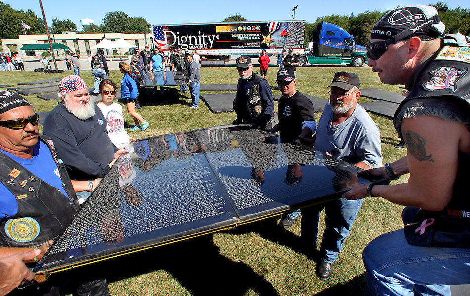 Panels bearing the names of those killed or missing in the Vietnam War are carried during assembly of The Dignity Memorial Vietnam Wall Wednesday at Resthaven Cemetery in West Des Moines. Jeff Kerr, right, of Ankeny helps lift with other volunteers.  The display, a traveling, three-quarter-scale replica of the Vietnam Veterans Memorial in Washington, D.C., will be open to school children on Thursday and to the public at  from Friday to Sunday. The faux-granite replica is 240 feet long, eight feet high and contains the names of more than 58,000 Americans who died or are missing in Vietnam. More than 30,000 people are expected to see the display while it is in West Des Moines.  (Christopher Gannon/The Des Moines Register) (Christopher Gannon/The Register)