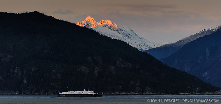 The final rays of the sun at sunset baths mountain tops in light as an Alaska Marine Highway System ferry travels down the Chilkoot Inlet of the Lynn Canal in this photo taken just outside Haines, Alaska. (John L. Dengler)