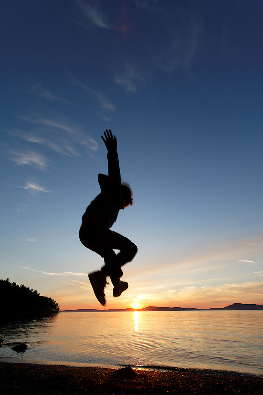 Girl leaping into the air above the setting sun, Sunset Beach, Washington Park, Anacortes, Skagit County, Washington (Brad Mitchell)