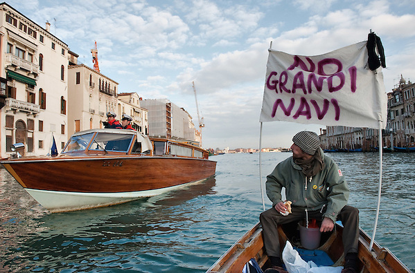 "VENICE, ITALY - JANUARY 16:  A protester, sailing next to a Coast Guard power boat on the Grand Canal, holds black listed banner reading ""Stop the large Ships""  on the day of the special meeting discussing the environmental impact of cruises in Venice on January 16, 2012 in Venice, Italy. Protest are mounting in Venice against large cruise ships crossing St Marks's basin after the Costa Concordia tragedy. (Marco Secchi)"