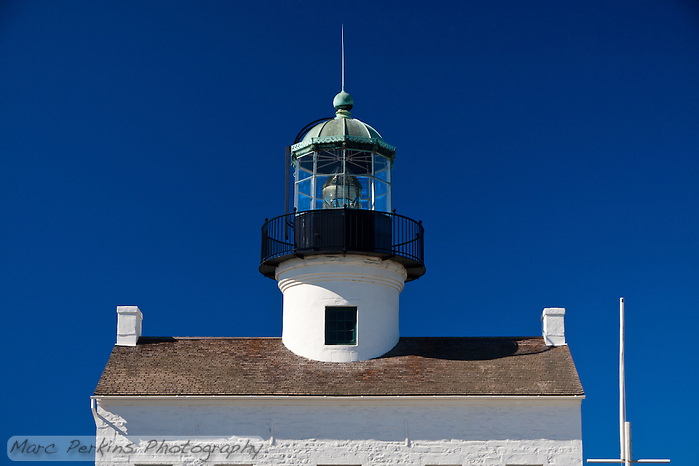 A somewhat cropped view of Old Point Loma Light as seen from the east on a crystal clear blue sky winter's day.    The bright white painted brick building contrasts with the clear blue sky and black lantern room.  The flagpole (currently lacking a flag) can be seen to the right of the house.  The windows of the lighthouse are just barely visible at the bottom of the crop.  While I generally prefer pictures of lighthouses either tightly cropped or whole with their surroundings3, I find this view of the house to be strangely entrancing.  It seems to be standing alone in front of a clear blue sky; what's before it and behind it are unknown, open to the viewer to decide. (Marc C. Perkins)