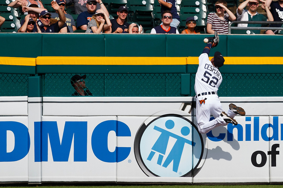 Jun 14, 2015; Detroit, MI, USA; Detroit Tigers left fielder Yoenis Cespedes (52) leaps onto the left field wall in an attempt to catch a ball hit by Cleveland Indians right fielder Brandon Moss (not pictured) for a home run in the ninth inning at Comerica Park. Detroit won 8-1. Mandatory Credit: Rick Osentoski-USA TODAY Sports (Rick Osentoski/Rick Osentoski-USA TODAY Sports)