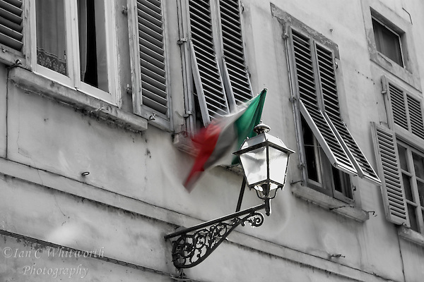 An Italian flag moving the the breeze in a street view with window shutters (Ian C Whitworth)
