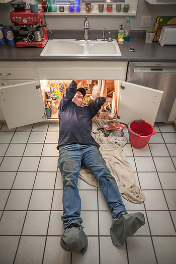 "Plumber Robert Boca fixes a leak in the kitchen sink at Clark and Mitzi's house in Calistoga, CA 707-227-0024. ""It's been a busy day with all the rain...lots of sup-pumps failing."" (© Clark James Mishler)"