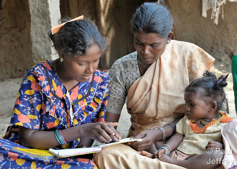 Angali (left) helps Jayalakstimi, who holds her daughter Kirthana, during a women's literacy class in Nandambakkam, a tribal village in the southern India state of Tamil Nadu. (Paul Jeffrey)
