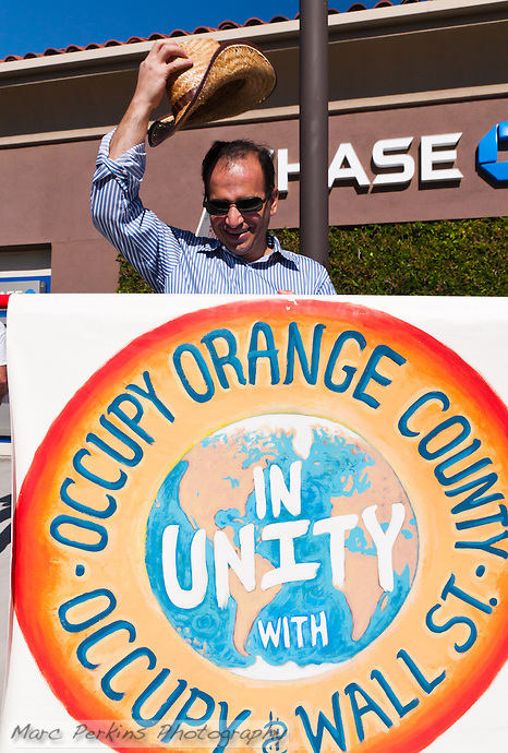 "Fred holds the primary ""Occupy Orange County, in unity with Occupy Wall Street"" sign in front of a Chase Bank branch during the the Occupy Orange County, Irvine march to three banks on November 5.  He's even raising his hat to the camera. (Marc C. Perkins)"