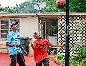 Rodney Smith Jr. watches as Quay Knight makes a basket, Aug. 1, 2018, in Huntsville, Ala. Quay, along with his brother, Lamar, is among more than 250 youth cutting grass as part of Raising Men Lawn Care Service, a non-profit organization Smith founded which provides free lawn care for the elderly, disabled, veterans, and single mothers. (Photo by Carmen K. Sisson) (Carmen K. Sisson/Cloudybright)