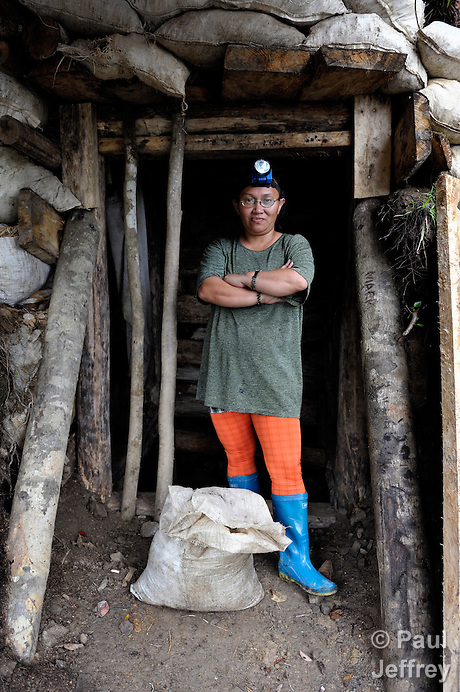 Daylien Elejorde stands at the opening of a gold mine she operates with her husband in the Diwalwal area on the Philippines' southern island of Mindanao. Hers is one of several mining families fighting back against plans to displace them by the Philippine Mining Development Corporation, a front company for foreign mining companies that seeks to install a large-scale open pit gold mine in the area. The small miners were given notice to evacuate the area by June 5, 2012, or risk being forcibly removed by the military. But Elejorde, a 43-year old Catholic catechist, and the other miners have defiantly refused to leave, and have formed a formal association to demand respect for their rights in the Philippines courts. .