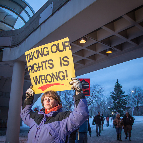Matsu Valley teacher, Dianne Wagner holds a sign protesting the loss of Municipal Union barganing power outside of the Anchorage Assembly Chambers in the Loussac Pulbic Library in midtown Anchorage. (Clark James Mishler)