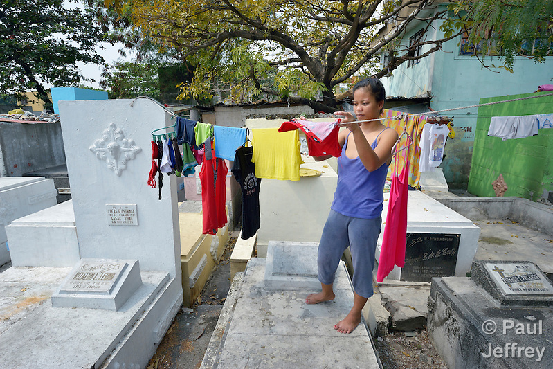 "In the capital of the Philippines, Aramay Calma hangs laundry over tombs in the Manila North Cemetery, where she lives. Hundreds of poor families live here, dwelling in and between the tombs and mausoleums of the city's wealthy. They are often discriminated against, and many of their children don't go to school because they're too hungry to study and they're often called ""vampires"" by their classmates. With support from United Methodist Women, KKFI provides classroom education and meals to kids from the cemetery at a nearby United Methodist Church. (Paul Jeffrey)"
