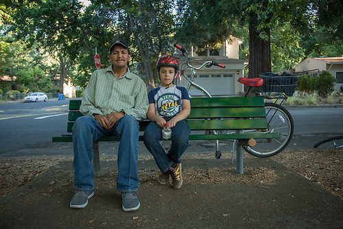 "Miguel Castro with his ight year old son, Miquel on a bench near Calistoga Elementary School.  ""We ride bicycles every night...tonight we rode out to the Guyser to see where the fire was.""  707-942-0497 (Clark James Mishler)"