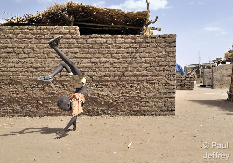 A displaced boy does a handstand in a camp outside Zalingei, in Sudan's war-torn Darfur region. (Paul Jeffrey)