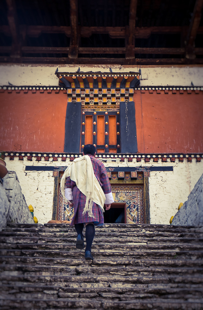 PARO, BHUTAN - CIRCA October 2014: Bhutamese man walking into the Paro Rinpung Dzong in Bhutan (Daniel Korzeniewski)