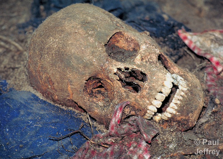 The skull of a man murdered in July 1982 by Guatemalan soldiers as they swept through the Maya highland village of Tabil. Eighteen people in the village were assassinated by the U.S.-backed soldiers and buried in two mass graves. In 1997, the Catholic Church helped the villagers exhume the bodies, identify the remains, and rebury them properly. (Paul Jeffrey)