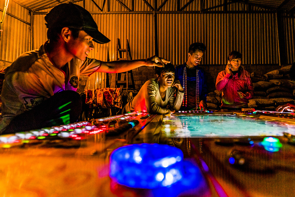 The young crowd plays an electronic game inside a barn in the town of Y Ty, Lao Cai Province. I think it might have been the only form of entertainment in the town…beyond drinking of course! Image by @quinnryanmattingly (Quinn Ryan Mattingly)