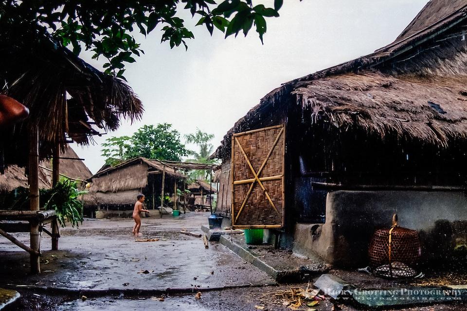 Nusa Tenggara, Lombok, Sade. Sade village. A sasak child playing in the rain. (Bjorn Grotting)