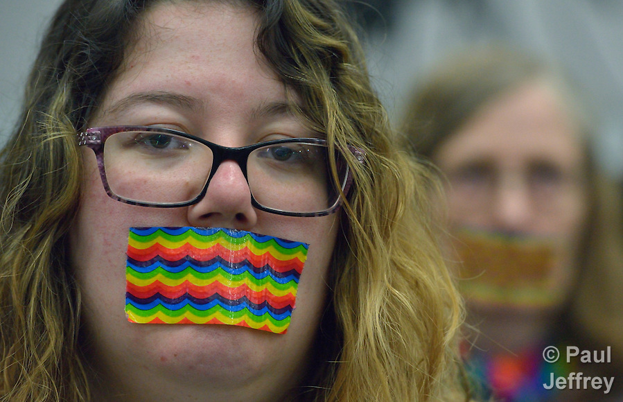 "Demonstrators wear rainbow gags on May 14 to protest what they believe is an attempt to silence LGBTQ voices during the 2016 United Methodist General Conference in Portland, Ore. The silent protest took place at the edge of a plenary session of the conference. The United Methodist Church does not authorize the ordination of ""self-avowed practicing homosexuals,"" but activists have for years demonstrated in favor of change at the quadrennial gathering of the world-wide denomination. Photo by Paul Jeffrey. (Paul Jeffrey)"