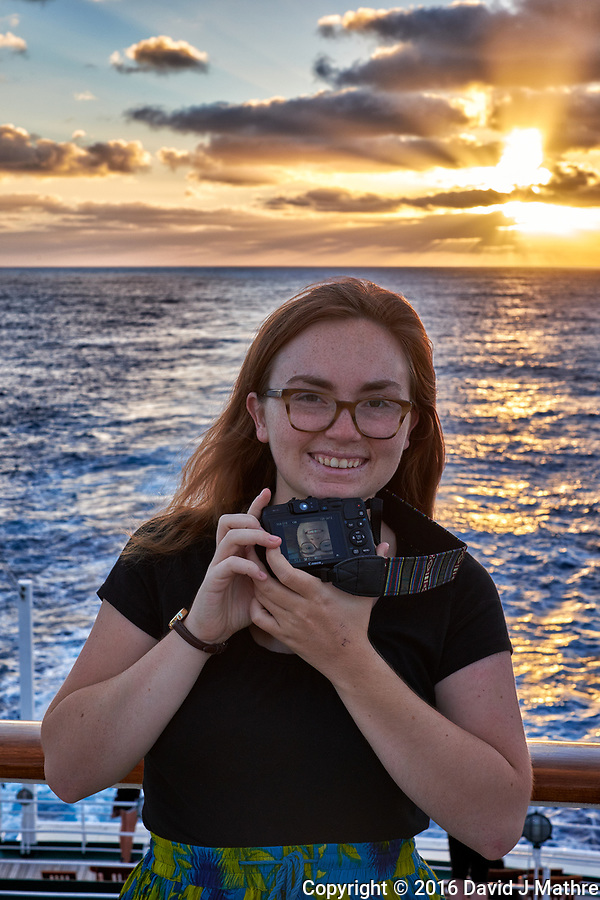 Student photographer at sunrise showing me her selfie otn the deck of the MV World Odyssey. Image taken with a Fuji X-T1 camera and 35 mm f/1.4 lens (ISO 200, 35 mm, f/5.6, 1/125 sec). (David J Mathre)