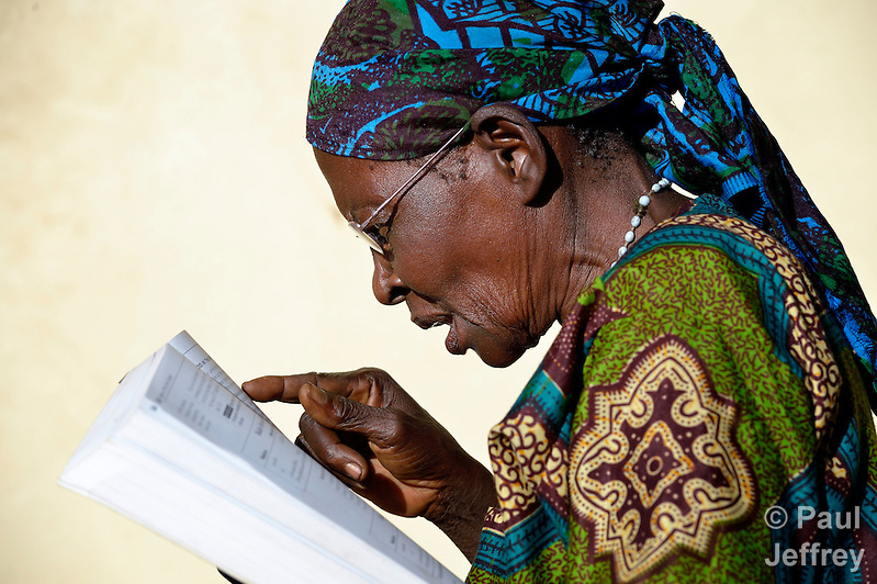 "Katherine Chimoteo, a woman in Riimenze, South Sudan, who says she is ""about 70"", reads for the first time in years after finding some glasses that worked for her in a box of used glasses. She's reading aloud from ""Where Women Have No Doctor"".. (Paul Jeffrey)"