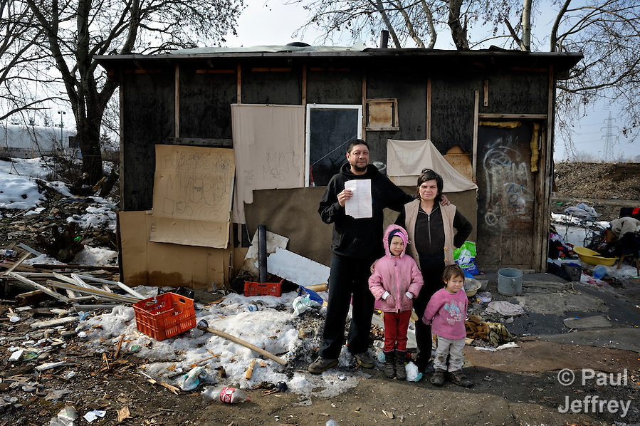 Vita Stankovic and his wife Arbanac Sofija, along with their daughters Rada, 5, and Caka, 3, stand in early 2012 outside their meager home in an illegal Roma settlement in Belgrade, Serbia. In February 2012, the family received the letter that Stankovic is holding informing them they will be evicted by city officials in March 2012 to make way for new high-rise office buildings.  In April 2012, the Serbian Orthodox family was forcibly evicted from the city center and given a metal shipping container in Makis, at the edge of Belgrade, where they could live. After several weeks, they were evicted from the shipping container because of Stankovic's repeated fights with his neighbors, and at the end of 2012 lived in an informal Roma squatter settlement in nearby Palilula. In 2009, they had been evicted from another settlement in Belgrade.. (Paul Jeffrey)