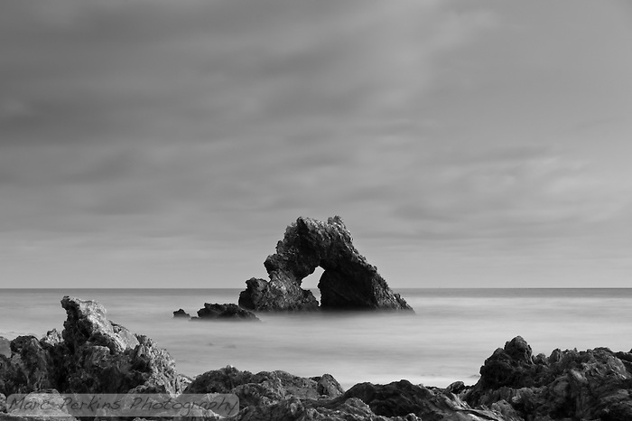 The arch rock at Little Corona seen on a cloudy evening just after sunset.  I love the soft dusk lighting illumindating the diffuse clouds overhead.  The image is a long exposure, so the ocean's waves have morphed into a silky smooth misty layer. (Marc C. Perkins)