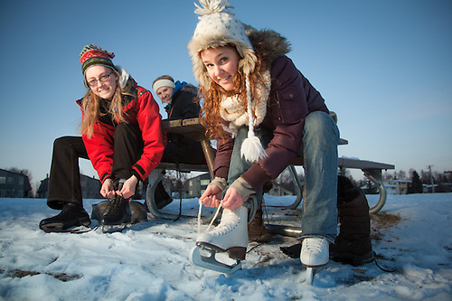 Covenant House voluteers, Rose Aspholm, Lauren Bajda, and Monica Stoesser, strap on their skates for the first skate of the season at Westchester Lagoon, Anchorage. (Clark James Mishler)