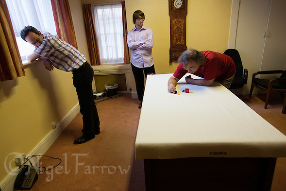 24 OCT 2013 - CAMBRIDGE, GBR - Challenger Patrick Barrie (GBR) (left) of Great Britain watches from a distance having hopefully put his opponent, the title holder Larry Kahn (USA) (right) of the USA, into a difficult position during tiddlywinks World Singles 67 in Barrie's office at Emmanuel College, Cambridge, Great Britain. (PHOTO COPYRIGHT © 2013 NIGEL FARROW, ALL RIGHTS RESERVED) (NIGEL FARROW/COPYRIGHT © 2013 NIGEL FARROW : www.nigelfarrow.com)
