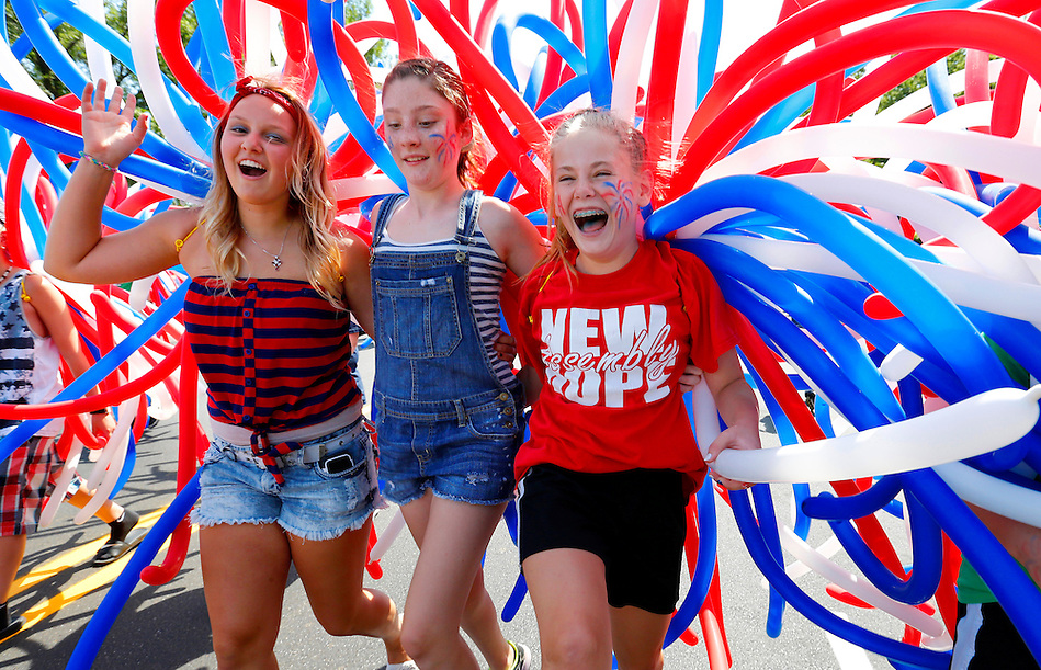 From left, Ashton Smith, 14, of Urbandale, Taryn Mock, 11, of Johnston and Delaney Phillips, 12, of Johnson revel patriotic balloons while walking in the Independence Day parade Friday morning in Urbandale. (Christopher Gannon/The Register)