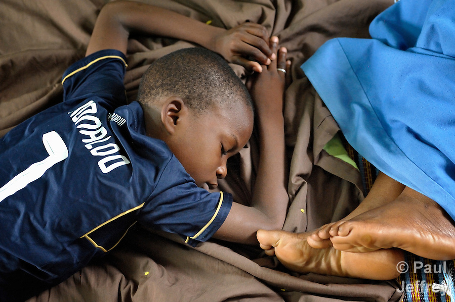 Two displaced children asleep on the floor inside a Catholic training center in Niamana, Mali. Several families displaced by the fighting in northern Mali took refuge in the center, and have received support from the ACT Alliance. (Paul Jeffrey)