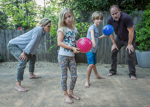 """We love family dodgeball...girls against the boys.  The boys beat up on us...they show no mercy.  Someday we will be victorious!""  -Genevieve Welsh with her husband, Thomas Brown, and children, Hazel (7) and Oscar (9), in the driveway of their home on Cedar Street in Calistoga. (Clark James Mishler)"