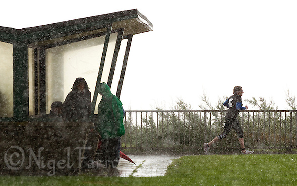 26 SEP 2010 - CLACTON, GBR - Spectators shelter from the rain as competitors make their way onto the run loop at the Clacton Standard Distance Triathlon (PHOTO (C) NIGEL FARROW) (NIGEL FARROW/(C) 2010 NIGEL FARROW)