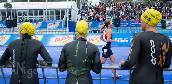 13 SEP 2013 - LONDON, GBR - Competitors waiting for their wave start watch Lucy Smith (GBR) of Great Britain on her run at the ITU 2013 World Age Group Sprint Distance Triathlon Championships in Hyde Park in London, Great Britain. Smith won gold in the women's 20-24 age group category (PHOTO COPYRIGHT © 2013 NIGEL FARROW, ALL RIGHTS RESERVED) (NIGEL FARROW/COPYRIGHT © 2013 NIGEL FARROW : www.nigelfarrow.com)