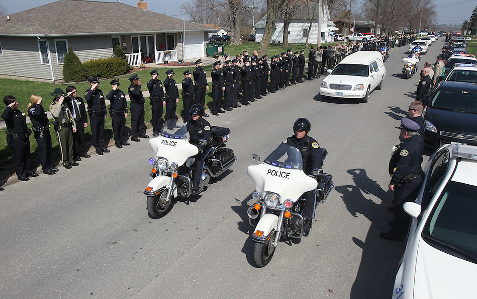 Hundreds of law enforcement officers line the street to salute the hearse carrying Sgt. Eric Stein as it passes Saturday, April 9 in Sigourney.  Stein was shot and killed in the line of duty. (Christopher Gannon/The Register)