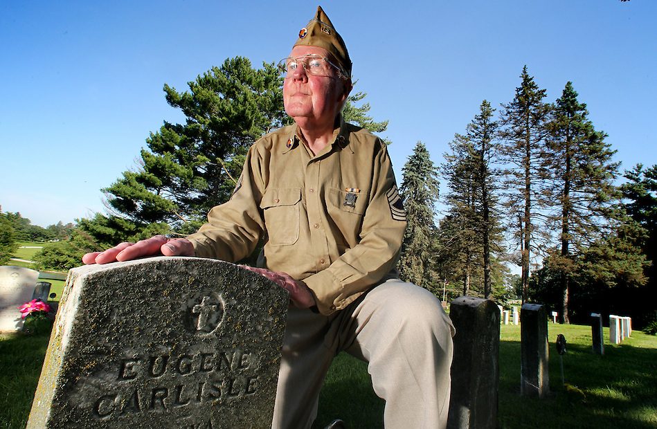 Gerald LeBlanc, a tireless advocate for the maintenance and repair of veterans' headstones, kneels with a row of aging Worls War I grave markers at Glendale Cemetery on June 30 in Des Moines. (Christopher Gannon/The Register)