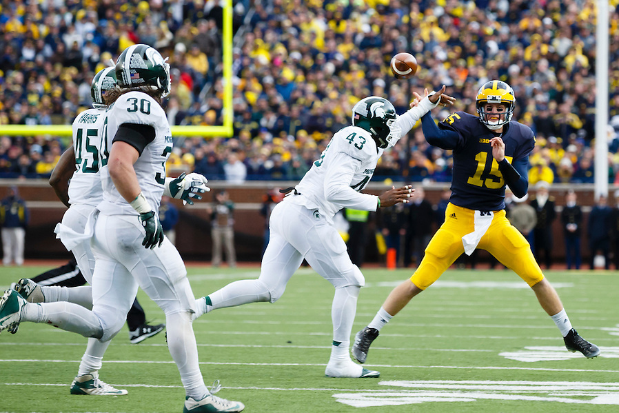 Oct 17, 2015; Ann Arbor, MI, USA; Michigan Wolverines quarterback Jake Rudock (15) throws the ball over Michigan State Spartans linebacker Ed Davis (43) during the third quarter  at Michigan Stadium. Mandatory Credit: Rick Osentoski-USA TODAY Sports (Rick Osentoski/Rick Osentoski-USA TODAY Sports)
