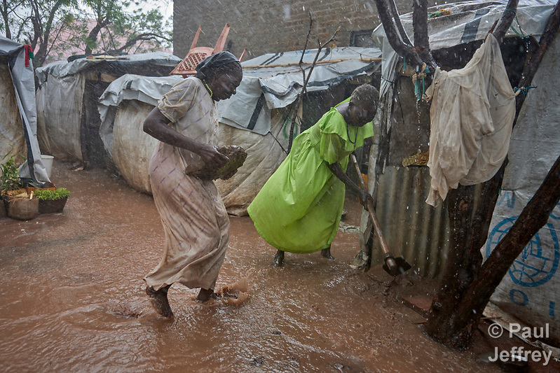 Rene Abdallah (left) and Anjima Fahal struggle to keep water out of their shelter during a heavy rainstorm in a displaced persons camp at the Holy Family Catholic Church in Wau, South Sudan. The church has provided food, shelter material, and health care, and the presence of clergy and religious has fostered a sense of relative safety for the families who first occupied the church grounds when fighting enveloped the city in 2016. (Paul Jeffrey)