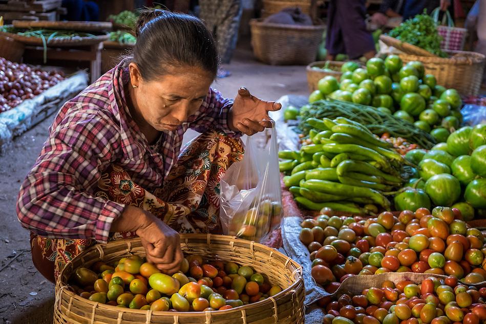 BAGAN, MYANMAR - CIRCA DECEMBER 2013: Burmese woman buying vegetables in the Nyaung U market close to Bagan in Myanmar (Daniel Korzeniewski)