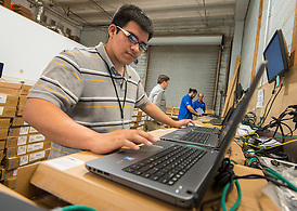Sharpstown High School 2014 graduate Jairo Luna prepares laptops at a NetSync warehouse for distribution to classrooms, July 2, 2014. The Sharpstown PowerUp coordinator recommended Luna for the internship. (Houston ISD/Dave Einsel)