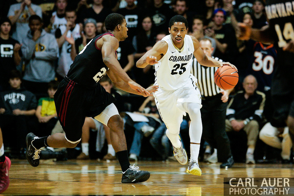 November 24th, 2013:  Colorado Buffaloes junior guard Spencer Dinwiddie (25) attempts to dribble the ball past Harvard Crimson junior guard/forward Wesley Saunders (23) in the second half of action in the NCAA Basketball game between the Harvard Crimson and the University of Colorado Buffaloes at the Coors Events Center in Boulder, Colorado (Carl Auer/ZUMAPRESS.com)