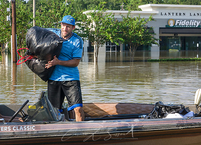 Volunteer Scott Sherman unloads a bag of wet clothes from a boat on Memorial Boulevard, Aug. 31, 2017, in Houston, Texas. Volunteers have streamed into Houston all week, sacrificing their time, money, and safety to help those affected by heavy flooding following Hurricane Harvey. (Photo by Carmen K. Sisson) (Carmen K. Sisson/Cloudybright)
