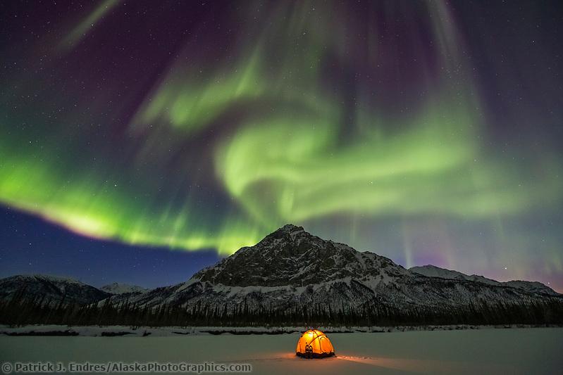 Northern lights over yellow tent and winter camp in the Brooks Range, Alaska. (Patrick J Endres / AlaskaPhotoGraphics.com)