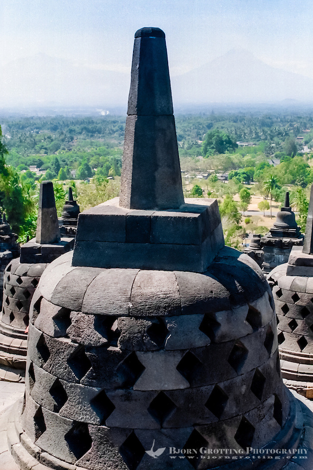 Java, Central Java, Borobodur. The three upper circular terraces carries 72 stupas, of which most contains a Buddha statue. The mount Merapi volcano in the background. (Photo Bjorn Grotting)