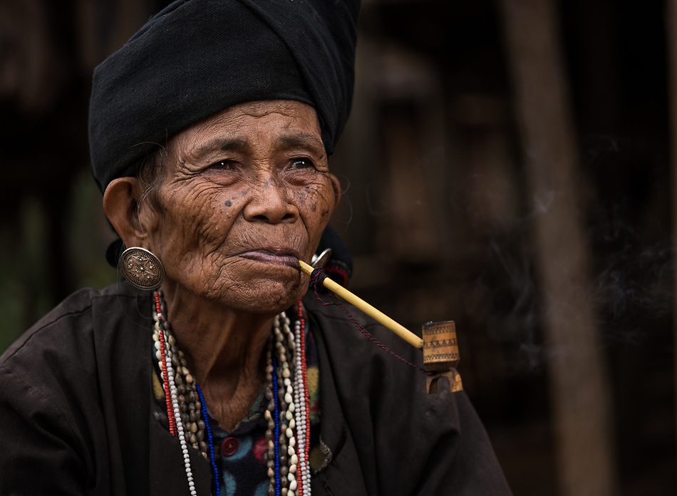 KYAING TONG, MYANMAR - CIRCA DECEMBER 2017: Portrait of elder woman of the Wan Sai Akha Village in Kyaing Tong smoking. (Daniel Korzeniewski)