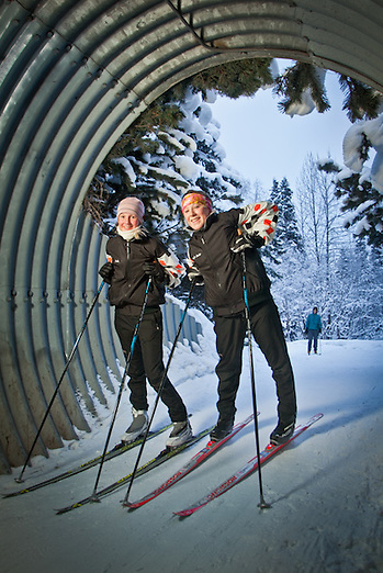 West High School cross country skiiers, Jojo Fleishman and Emily Decker, on the Tony Knowles Coastal Trail at the tunnel under I Street near Westchester Lagoon, Anchorage (Clark James Mishler)