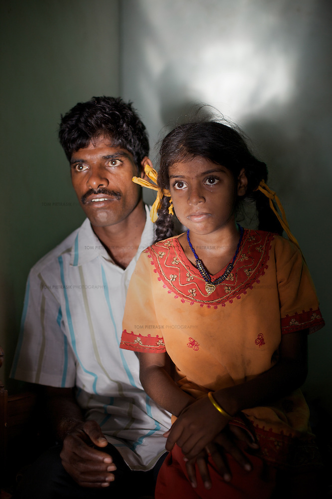 "Viswanathan with his daughter Vijyashree at home in the fishing village of Thazanguda, near Cuddalore. ..Vijita (age 14) and Vijyashree (age 11) Viswanathan lost their mother and brother to the tsunami in 2004. They continue to live in the fishing village of Thazanguda with their father Viswanathan, his second wife Kayalvizhi and their two children Sanjay (age 3) and Monica (age 1). ..Until the beginning of the 2009 academic year in June, Vijita and Vijyashree attended the local Thazanguda school. This village school teaches pupils only until the 8th Standard and with Vijita now entering the 9th, it was decided that the two daughters remain together and both travel 3km to the local town school: the Government Girls High School, Venugopalapuram in Cuddalore. ..At the same time Viswanathan decided he would cease day-to-day care of his daughters and place them in the Government Home for Tsunami Children, also in Cuddalore. This was not a move welcomed by either Vijita or Vijyashree and one afternoon after just two weeks at the orphanage, the two girls ran away. At roll call in the orphanage that evening the alarm was sounded and the two sisters were eventually located in Thazanguda waiting for their father and Kayalvizhi who were both away at the time. Realising his daughters' unhappiness, Viswanathan then took them out of the Government home. ..According to her class teacher, Vijita often compares her step-mother to her mother and concludes that she wants her mother back. Vijita confides in her teachers that her stepmother is forever demanding that she and her sister Vijyashree undertake housework. This frustration at home is tempered by the genuine love both sisters have for their father and two younger siblings Sanjay and Monica. Vijita expresses a lonelyness without her mother. Pushpavalli concludes that ""Vijita wants something else beyond the love of her father and sister"". ..Viswanathan appears genuinely to want the best for his two elder daughters. His experimen (Tom Pietrasik)"